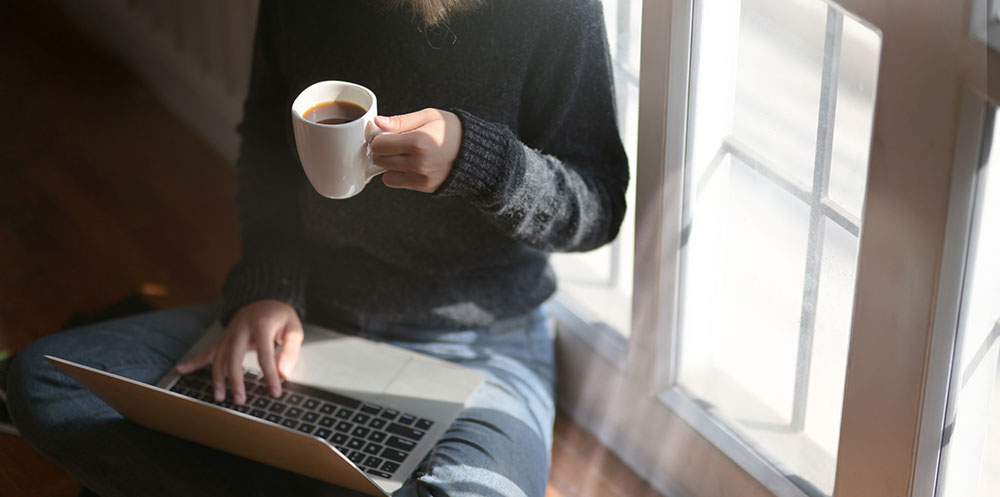 woman working from home using laptop while holding a cup of coffee